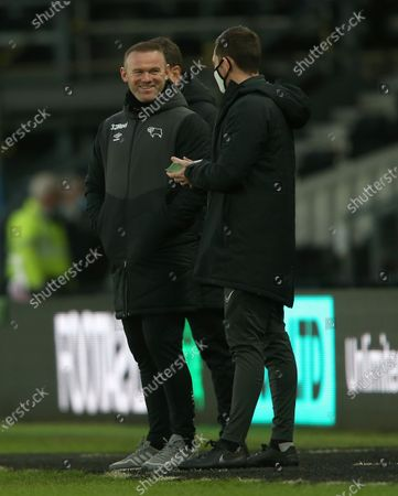 Derby County manager Wayne Rooney enjoys a joke with the fourth official Simon Mather