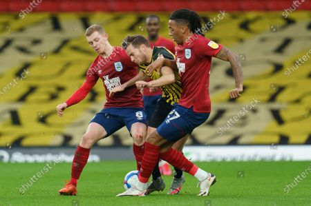 Tom Cleverley of Watford (8) is surrounded by Lewis O'Brien of Huddersfield Town (8) and Romoney Crichlow of Huddersfield Town (27)