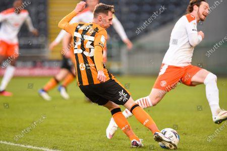Gavin Whyte of Hull City shoots at goal as James Husband of Blackpool blocks