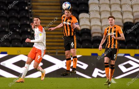 Richard Smallwood of Hull City clears as Jerry Yates of Blackpool and Reece Burke look on