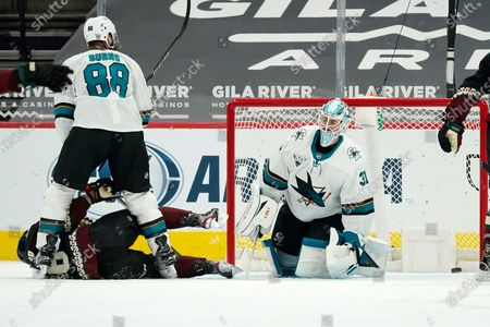 Stock Photo of San Jose Sharks goaltender Martin Jones (31) gives up a goal to Arizona Coyotes Conor Garland as Sharks defenseman Brent Burns (88) sends Coyotes center Derick Brassard to the ice during the second period of an NHL hockey game, in Glendale, Ariz