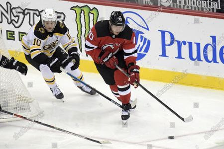 Boston Bruins left wing Anders Bjork (10) checks New Jersey Devils defenseman Dmitry Kulikov (70) during the second period of an NHL hockey game, in Newark, N.J