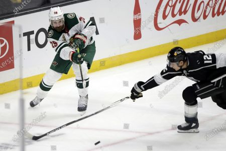 Minnesota Wild defenseman Greg Pateryn, left, passes the puck past Los Angeles Kings center Trevor Moore during the third period of an NHL hockey game in Los Angeles