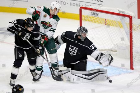 Los Angeles Kings goaltender Jonathan Quick, right, deflects a shot with Minnesota Wild center Nico Sturm, center, and center Trevor Moore watching during the third period of an NHL hockey game in Los Angeles