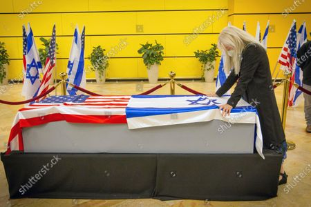 Miriam Adelson touches the casket of her husband, Sheldon Adelson upon arrival to Ben Gurion Airport, near the city of Lod, Israel, . Adelson, the billionaire mogul and power broker who built a casino empire spanning from Las Vegas to China and became a singular force in domestic and international politics has died after a long illness, his wife said Tuesday, Jan. 12, 2021