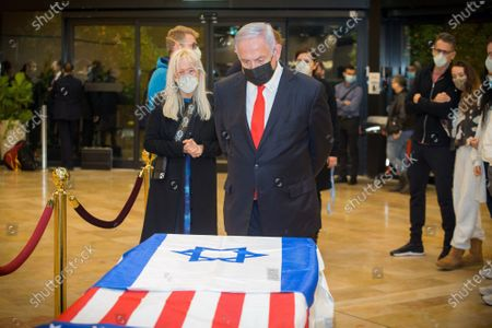 Israeli Prime Minister Benjamin Netanyahu stands before the casket of Sheldon Adelson, with his wife, Miriam Adelson, upon arrival to Ben Gurion Airport, near the city of Lod, Israel, Thursday, Jan. 14, 2021.  Adelson, the billionaire mogul and power broker who built a casino empire spanning from Las Vegas to China and became a singular force in U.S. domestic and international politics has died after a long illness, his wife said Tuesday, January 12, 2021.