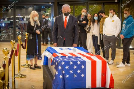 Israeli Prime Minister Benjamin Netanyahu stands before the casket of Sheldon Adelson upon arrival to Ben Gurion Airport, near the city of Lod, Israel, Thursday, January 14, 2021.  Adelson's family, including his wife, Miriam, at left, are present.  Adelson, the billionaire mogul and power broker who built a casino empire spanning from Las Vegas to China and became a singular force in U.S. domestic and international politics has died after a long illness, his wife said Tuesday, January 12, 2021.