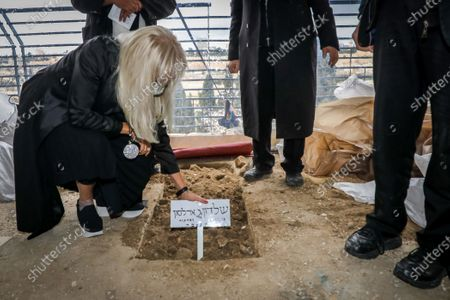 Miriam Adelson, mourns next to the grave of her husband philanthropist and businessman Sheldon Adelson during his funeral, in Jerusalem, 15 January 2021. Adelson, the billionaire mogul and power broker who built a casino empire spanning from Las Vegas to China and became a singular force in domestic and international politics has died after a long illness, on 11 January 2021 at the age of 87.