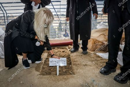 Miriam Adelson, mourns next to the grave of her husband, Sheldon Adelson, in Jerusalem, during his funeral