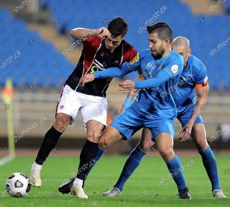 Al-Raed's player Nemanja Nikolic (L) in action against Al-Nassr's Petros (2-L) and Maicon (R) during the Saudi Professional League soccer match between Al-Raed and Al-Nassr at King Abdullah Sports City Stadium, in Buraidah, Saudi Arabia, 15 January 2021.