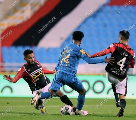 Al-Raed's players Abdullah Al-Fahad (L) and Khalid Al-Khathlan (R) in action against Al-Nassr's Sami Al-Najei (C) during the Saudi Professional League soccer match between Al-Raed and Al-Nassr at King Abdullah Sports City Stadium, in Buraidah, Saudi Arabia, 15 January 2021.