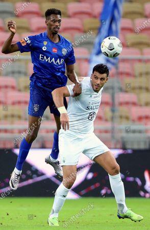 Al-Ahli's player Omar Al-Somah (R) in action against Al-Hilal's Mohamed Kanno (L) during the Saudi Professional League soccer match between Al-Ahli and Al-Hilal at King Abdullah Sport City Stadium, 30 kilometers north of Jeddah, Saudi Arabia, 15 January 2021.