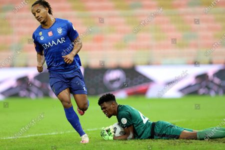 Al-Ahli's goalkeeper Mohammed Al Yami (R) in action against Al-Hilal's Andre Carrillo (L) during the Saudi Professional League soccer match between Al-Ahli and Al-Hilal at King Abdullah Sport City Stadium, 30 kilometers north of Jeddah, Saudi Arabia, 15 January 2021.