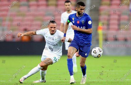 Al-Ahli's player Ljubomir Fejsa (L) in action against Al-Hilal's Salman Al-Faraj (R) during the Saudi Professional League soccer match between Al-Ahli and Al-Hilal at King Abdullah Sport City Stadium, 30 kilometers north of Jeddah, Saudi Arabia, 15 January 2021.