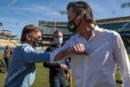 Stock Photo of US Actor Sean Penn, left, Los Angeles Mayor Eric Garcetti (C) and California Governor Gavin Newsom (R) greet each other at a press conference held at the launch of mass COVID-19 vaccination site at Dodger Stadium in Los Angeles, California, USA, 15 January 2021.