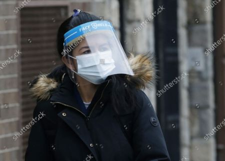 A woman walks on the sidewalk wearing a face mask and face shield before Secretary of State Rossana Rosado and New York State open another New York State vaccination site at Corsi Houses in East Harlem in New York City on Friday, January 15, 2021.