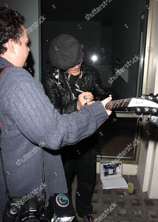 Photographer James Curley hands over his guitar to Adam Ant for signing.