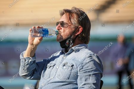 Sitting under blazing sun actor Sean Penn quenches his thirst during a press conference held at the launch of a mass COVID-19 vaccination site at Dodger Stadium, in Los Angeles