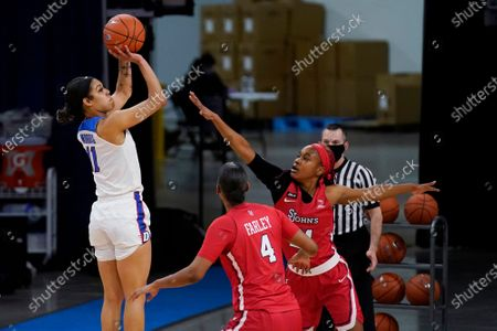 DePaul guard Sonya Morris, left, shoots against St. John's forward Raven Farley, center, and guard Qadashah Hoppie during the first half of an NCAA college basketball game in Chicago