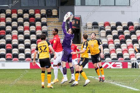 Newport County's Goalkeeper Tom King (1) claims the high ball from Salford City's Tom Elliott (9) during the EFL Sky Bet League 2 match between Newport County and Salford City at Rodney Parade, Newport