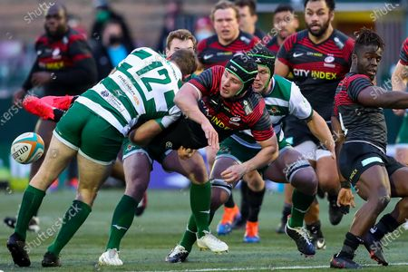 Harry Sloan of Saracens is tackled by Pat Howard of Ealing Trailfinders