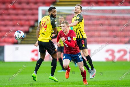 Huddersfield Town midfielder Lewis O'Brien (8) beats Watford midfielder Nathaniel Chalobah (14) and Watford midfielder Tom Cleverley (8) in a challenge during the EFL Sky Bet Championship match between Watford and Huddersfield Town at Vicarage Road, Watford