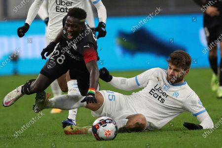 Nimes' Moussa Kone, left, is tackled by Marseille's Duje Caleta-Car during the French League One soccer match between Marseille and Nimes at the Veledrome stadium in Marseille, France, Saturday, Jan.16, 2021