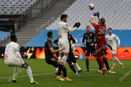 Nimes' goalkeeper Baptiste Reynet blocks a header by Marseille's Duje Caleta-Car during the French League One soccer match between Marseille and Nimes at the Veledrome stadium in Marseille, France, Saturday, Jan.16, 2021
