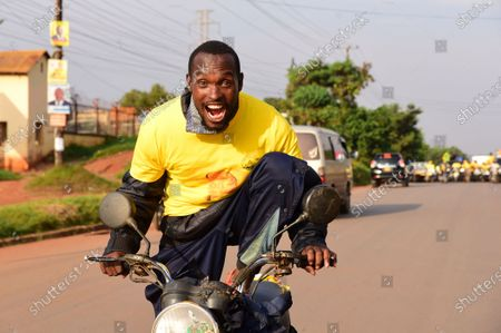 A supporter of incumbent Ugandan Presdent Yoveri Museveni celebrates as he rides a motorcycle in the streets of Kampala, Uganda, 16 January 2021. Uganda's electoral commission announced Yoweri Museveni has won a sixth term in office with almost 60 percent of votes.