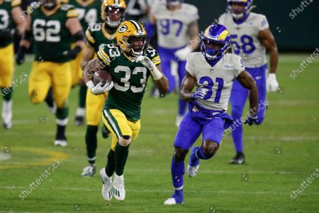 Stock Photo of Green Bay Packers' Aaron Jones (33) races against Los Angeles Rams' Darious Williams (31) during the second half of an NFL divisional playoff football game, in Green Bay, Wis