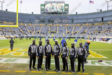 Game officials from left to right; head linesman Jim Howey (37), back judge Greg Yette (38), umpire Mark Pellis (131), referee Ron Torbert (62), side judge Jonah Monroe (120), field judge James Coleman (95) and line judge Rusty Baynes (59) pose beforebefore an NFL divisional playoff football game between the Los Angeles Rams and Green Bay Packers, in Green Bay, Wis