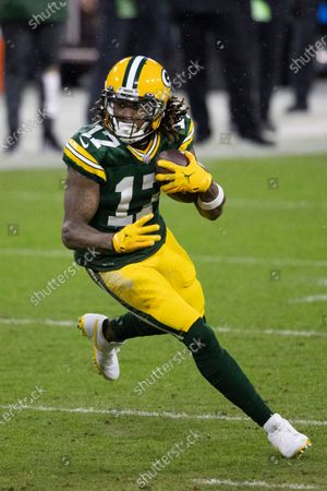 Green Bay Packers wide receiver Davante Adams (17) runs after a catch during an NFL divisional playoff football game between the Los Angeles Rams and Green Bay Packers, in Green Bay, Wis
