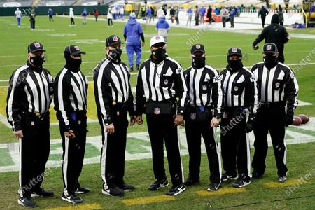 Game officials from left to right; head linesman Jim Howey (37), back judge Greg Yette (38), umpire Mark Pellis (131), referee Ron Torbert (62), side judge Jonah Monroe (120), field judge James Coleman (95) and line judge Rusty Baynes (59) pose before an NFL divisional playoff football game between the Los Angeles Rams and Green Bay Packers, in Green Bay, Wis