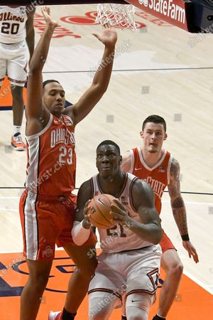 Illinois center Kofi Cockburn (21) looks for an open shot as Ohio State's center Zed Key (23) and forward Kyle Young (25) defend in the second half of an NCAA college basketball game, in Champaign, Ill