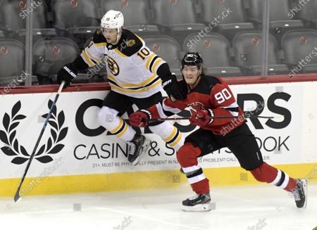 Boston Bruins left wing Anders Bjork (10) attempts to get by New Jersey Devils center Jesper Boqvist (90) during the first period of an NHL hockey game, in Newark, N.J