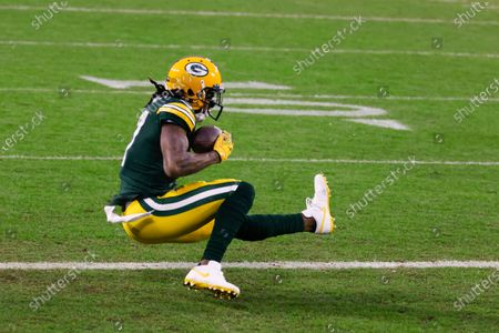 Green Bay Packers' Davante Adams catches a touchdown pass from Aaron Rodgers during the first half of an NFL divisional playoff football game against the Los Angeles Rams, in Green Bay, Wis