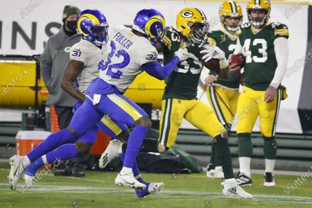 Stock Image of Los Angeles Rams' Jordan Fuller (32) tackles Green Bay Packers' Aaron Jones (33) during the second half of an NFL divisional playoff football game, in Green Bay, Wis