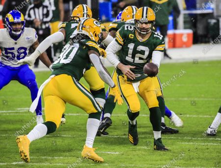 Green Bay Packers quarterback Aaron Rodgers (R) hands the ball to Green Bay Packers running back Jamaal Williams (L) during the NFL Divisional playoff game between the Los Angeles Rams and the Green Bay Packers at Lambeau Field in Green Bay, Wisconsin, USA, 16 January 2021.
