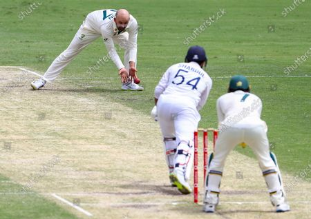 Australia's Nathan Lyon fields the ball hit by India's Shardul Thakur during play on day three of the fourth cricket test between India and Australia at the Gabba, Brisbane, Australia