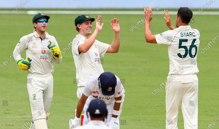Australia's Mitchell Starc, right, is congratulated by teammate Cameron Green after taking the wicket of India's Ajinkya Rahane during play on day three of the fourth cricket test between India and Australia at the Gabba, Brisbane, Australia