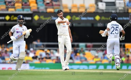 Mitchell Starc (centre) of Australia is seen reacting during day three of the fourth Test Match between Australia and India at the Gabba in Brisbane, Australia, 17 January 2021.