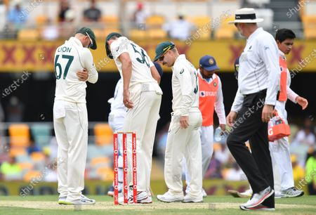 Nathan Lyon (L), Mitchell Starc (C) and David Warner (R) of Australia are seen looking at the pitch during day three of the fourth Test Match between Australia and India at the Gabba in Brisbane, Australia, 17 January 2021.