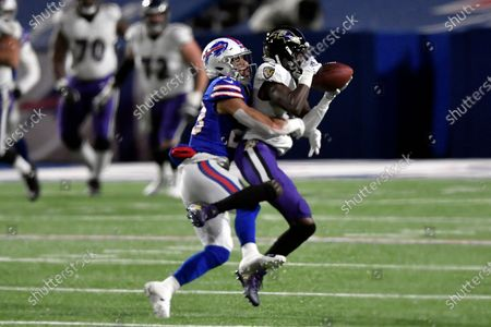 Baltimore Ravens wide receiver Marquise Brown, right, catches a pass in front of Buffalo Bills' Micah Hyde, left, during the first half of an NFL divisional round football game, in Orchard Park, N.Y