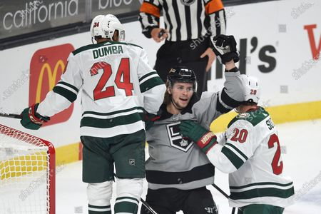 Los Angeles Kings right wing Adrian Kempe, center, celebrates after a goal by Gabriel Vilardi while Minnesota Wild defensemen Mathew Dumba, left, and Ryan Suter look on during the first period of an NHL hockey game in Los Angeles