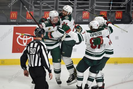 Minnesota Wild defenseman Mathew Dumba (24) congratulates defenseman Ryan Suter, left, on a game-tying goal during the third period of the team's NHL hockey game against the Los Angeles Kings in Los Angeles