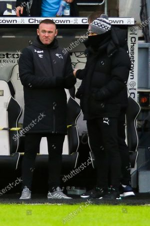 Derby County manager Wayne Rooney talks with Rotherham United manager Paul Warne