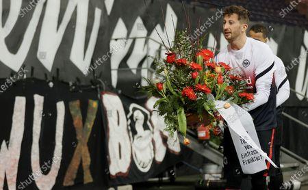 Frankfurt's David Abraham lays flowers to commemorate a deceased Eintracht Frankfurt fan before the German Bundesliga soccer match between Eintracht Frankfurt and FC Schalke 04 in Frankfurt, Germany, 17 January 2021.