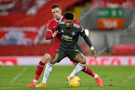 Stock Image of Liverpool's Jordan Henderson vies for the ball with Manchester United's Marcus Rashford, right, during the English Premier League soccer match between Liverpool and Manchester United at Anfield Stadium, Liverpool, England