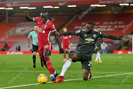 Manchester United's Aaron Wan-Bissaka vies for the ball with Liverpool's Sadio Mane, left, during the English Premier League soccer match between Liverpool and Manchester United at Anfield Stadium, Liverpool, England
