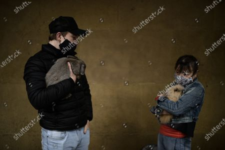 Manoli, right, wears face mask protection to prevent the spread to the coronavirus, holds her rabbit pet close to her son while waiting to be blessing during the feast of St. Anthony, Spain's patron saint of animals, in Pamplona, northern Spain, . The feast is celebrated each year in many parts of Spain and people bring their pets to churches to be blessed